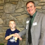 Travis receiving Gold Award from Dr. Dan Smith, West District Extension Director