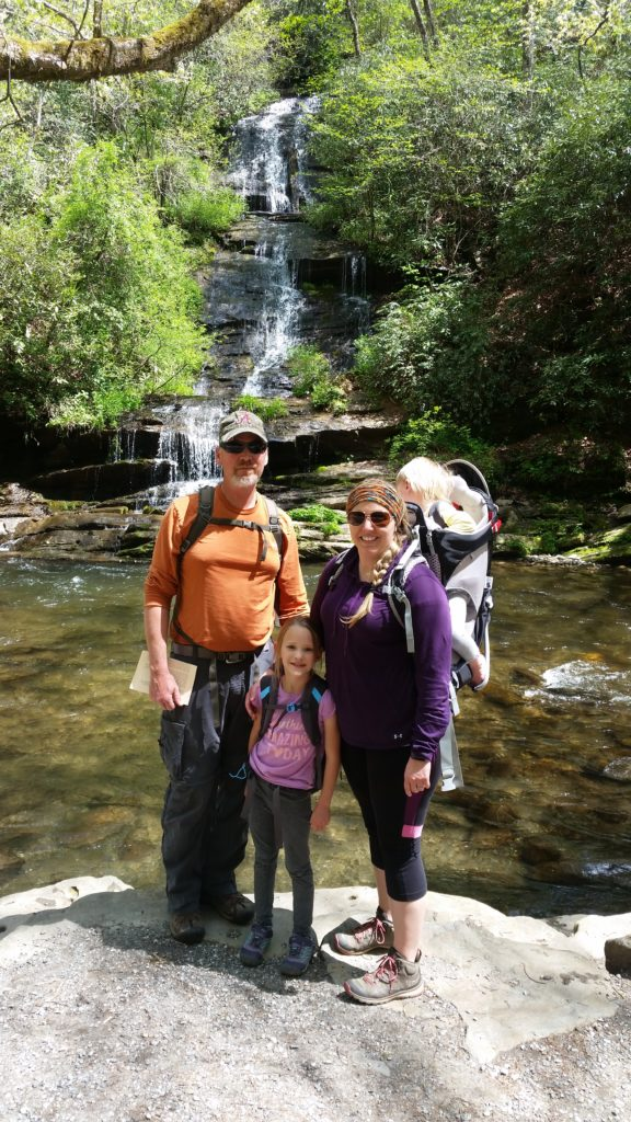 Gibbs family posing by a small waterfall on their hike